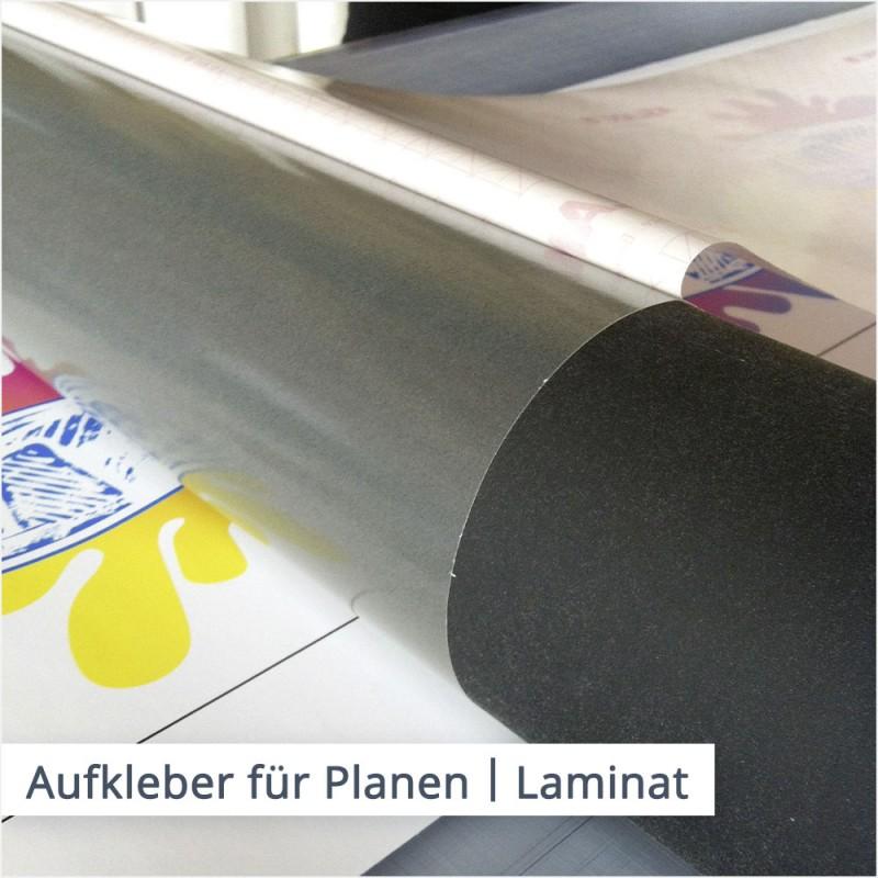 Eine fertig gedruckter Aufkleber für Planen wird mit dem dünnen, transparenten Schutzlaminat kaschiert.