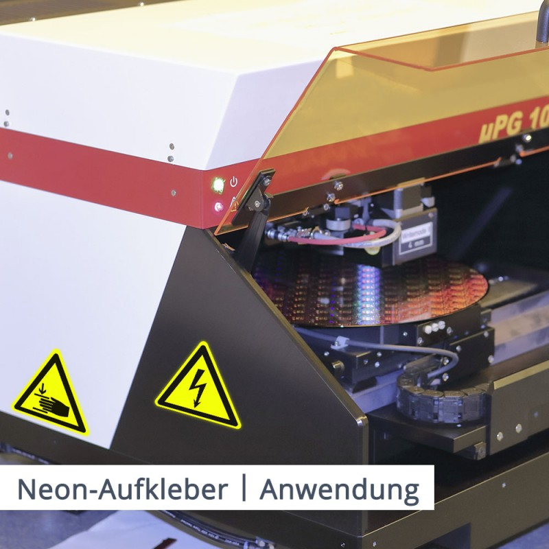 Sicherheitshinweise auf großen Maschinen sind mit gelben Neon Aufkleber deutlich erkennbar.